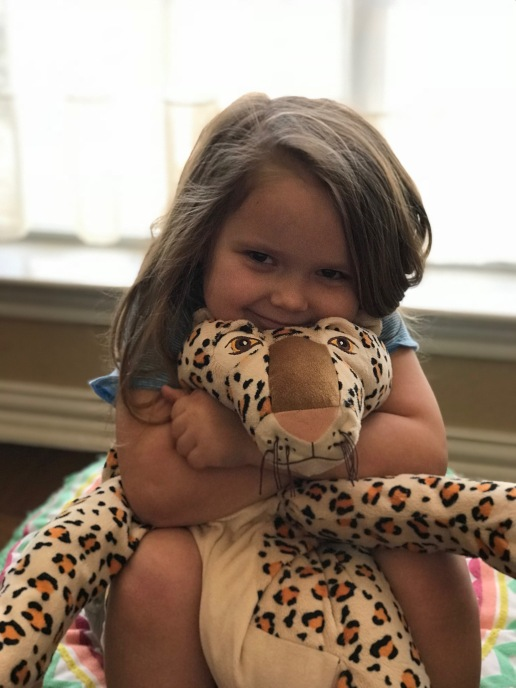 Ella loves to squeeze her stuffed leopard.